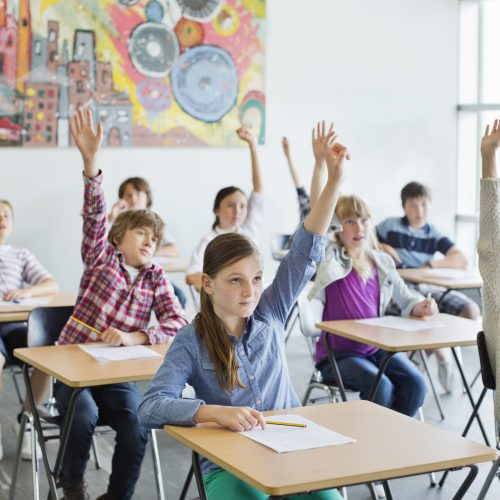 Students with arms raised in classroom